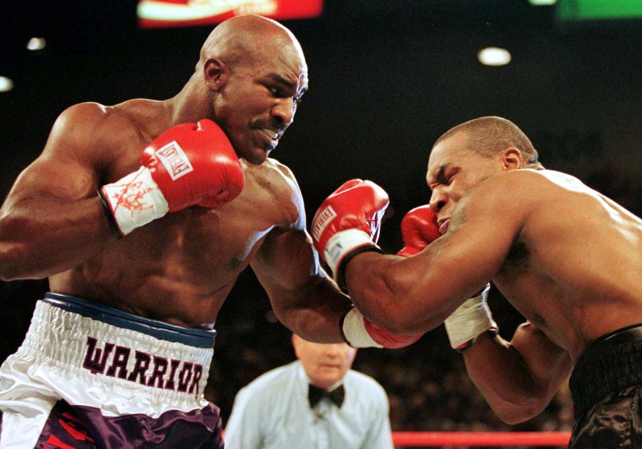 Evander Holyfield (L) en  Mike Tyson in de eerste ronde van hun titelgevecht op 28 juni 1997