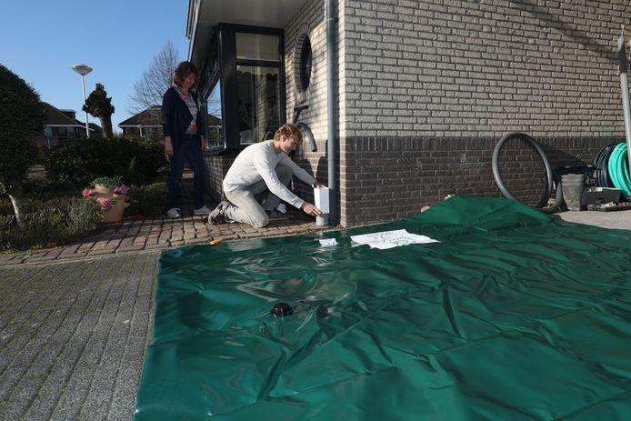 Carmen Ekas kijkt toe hoe Iwan Fransen een filter installeert voor het regenwateropvangsysteem onder haar woning.