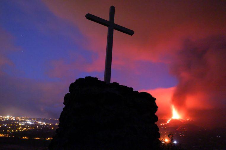 Een kruis met een vulkaanuitbarsting op de achtergrond.  Beeld REUTERS