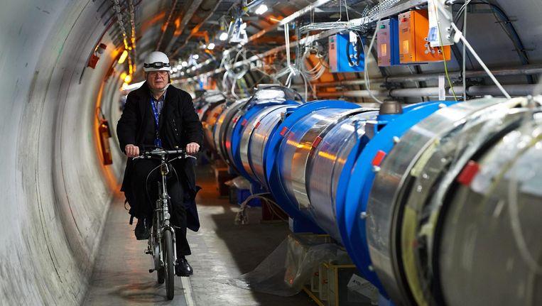 De Poolse wetenschapper Andrzej Siemko fietst langs de LHC-deeltjesversneller in Meyrin, nabij Gèneve. Beeld epa