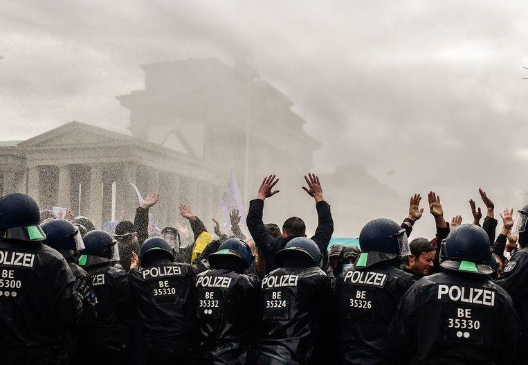 Botsing tussen politie en demonstranten bij een manifestatie tegen de coronamaatregelen in Berlijn. De politie verrichte 365 arrestaties en zette waterkannonen en traangas in om de menigte uiteen te drijven. Beeld EPA