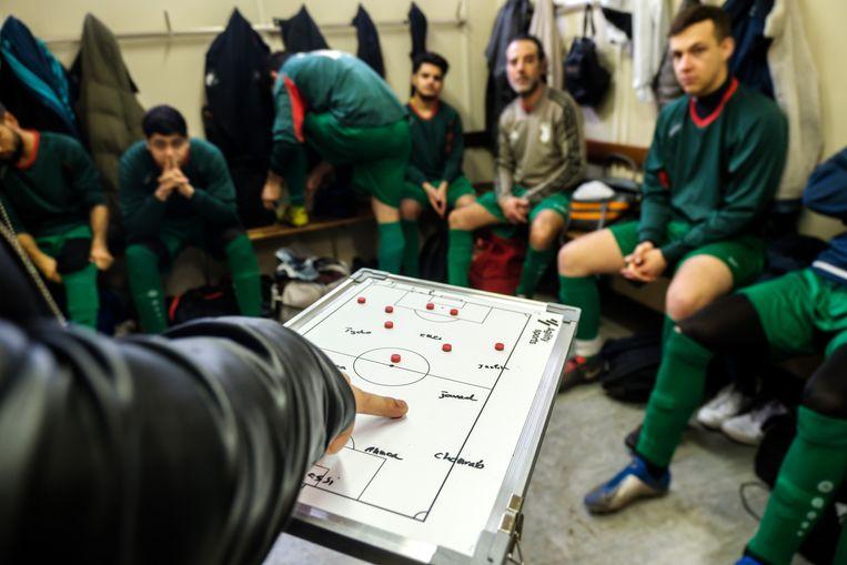 Coach Farhood legt de strategie voor de komende match uit aan de mannen.