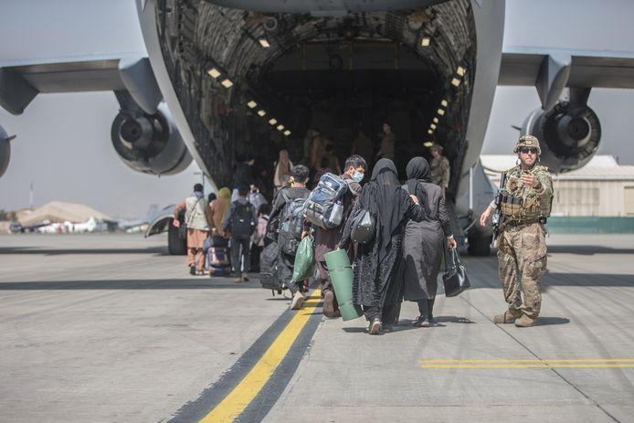Vluchtelingen stappen in een toestel van het Amerikaanse leger