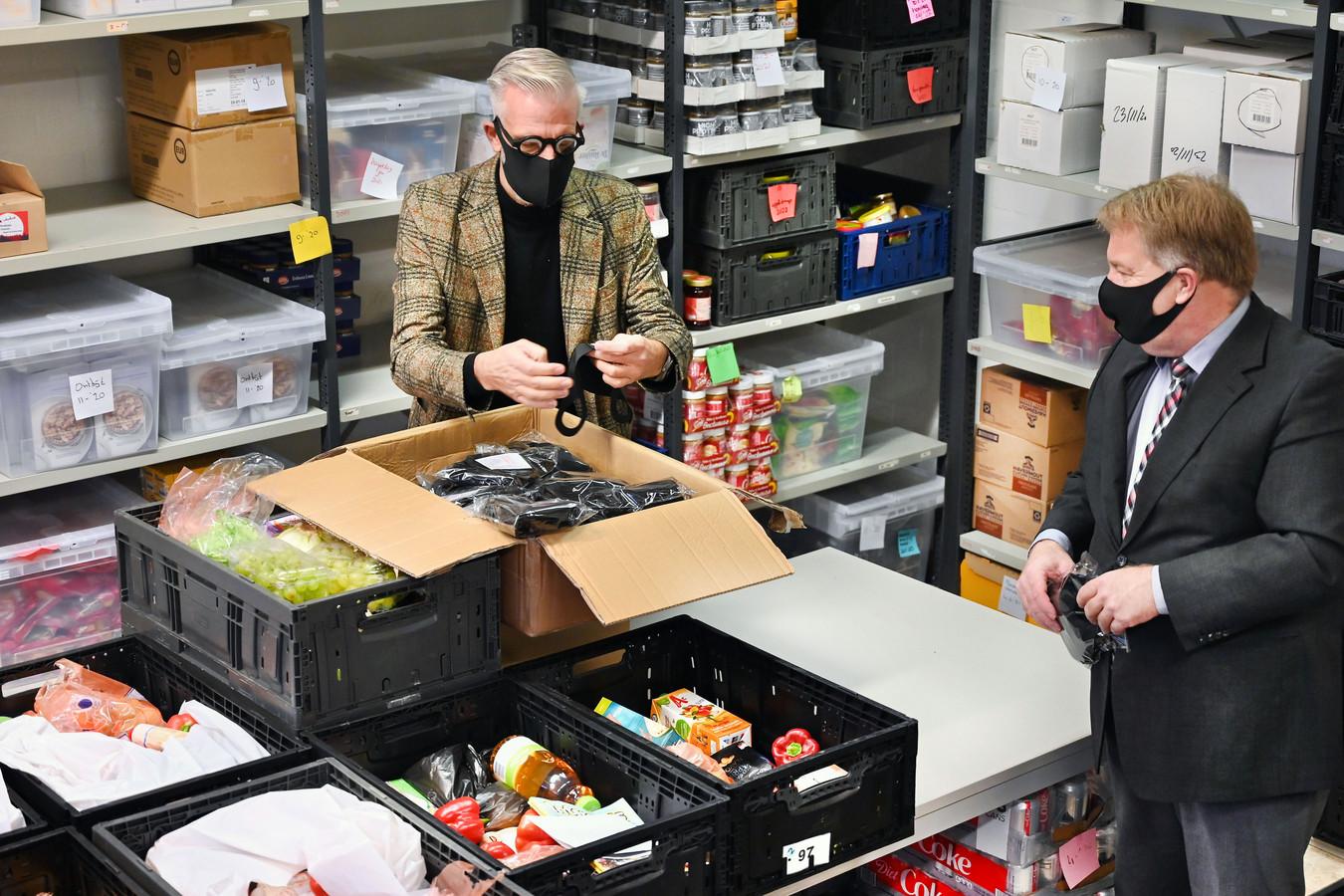 Wethouder Adrie Bragt (rechts) levert namens de gemeenten Zaltbommel en Maasdriel een partij mondkapjes af bij de Voedselbank Bommelerwaard.