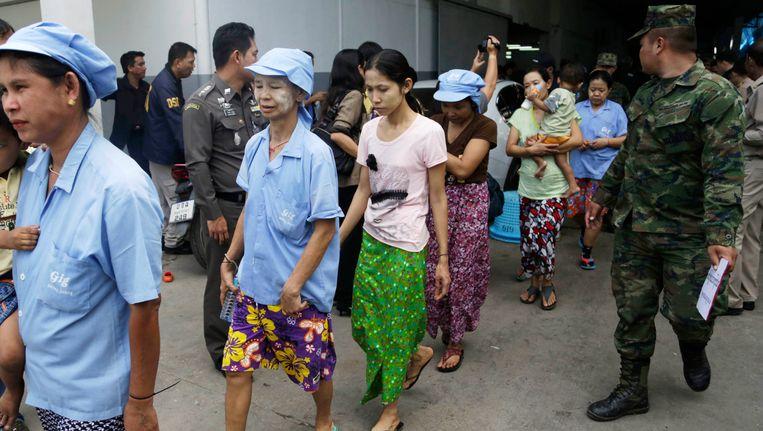 Birmese slaven worden uit een garnalenfabriek begeleid onder toezicht van soldaten en politieagenten na een inval. Beeld AP