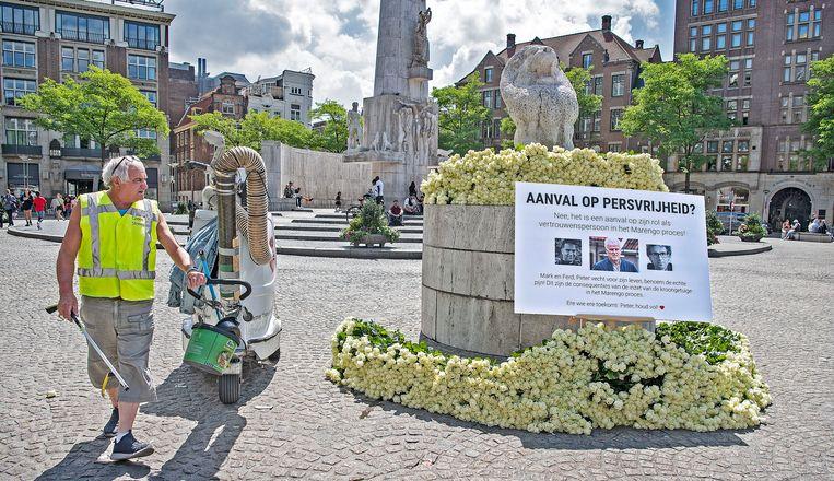 Witte rozen voor Peter R. de Vries op de Dam, waarbij de tekst meldt dat het niet gaat om een aanval op de persvrijheid, maar om De Vries' rol als vertrouwenspersoon bij Marengo-proces.  Beeld Guus Dubbelman / de Volkskrant