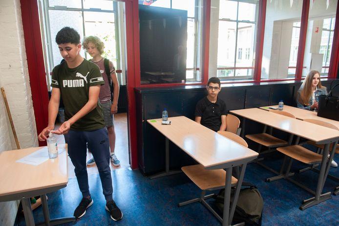 Bij binnenkomst in het klaslokaal van het Sint-Janslyceum in Den Bosch moeten de leerlingen eerst hun handen desinfecteren. De tafels zijn zo verschoven dat 1,5 meter afstand gewaarborgd is.