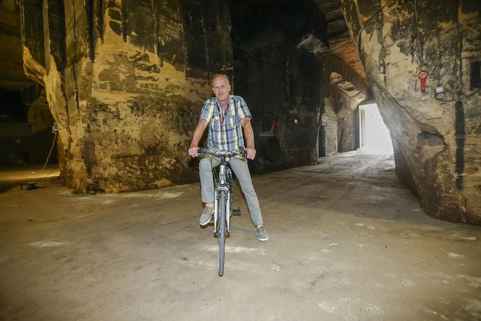 Schepen Christian Bamps op de fiets in een mergelgrot van de Putberg.