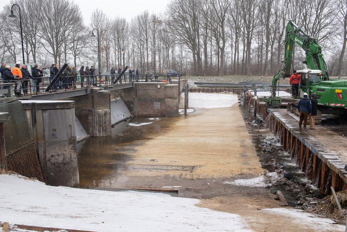 Buurman Freddy Bril mag samen met bestuurslid Stegeman van waterschap Vechtstromen een deel van de damwand met een zware kraan naar beneden drukken, waarna het rivierwater de nieuw gestorte ontvangstvloer van stuw De Haandrik overspoelt.