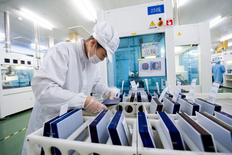 Februari 2011, Suntech-werknemer Sun Jun checks controleert zonnecellen in de fabriek in Wuxi. Beeld Lucas Schifres / Getty