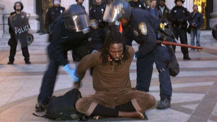 Politie houdt een occupy-betoger vast.