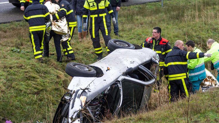 Brandweerlieden helpen inzittenden van een auto op het droge nadat zij door een verkeersruzie op de A58 in de sloot waren beland. Beeld anp