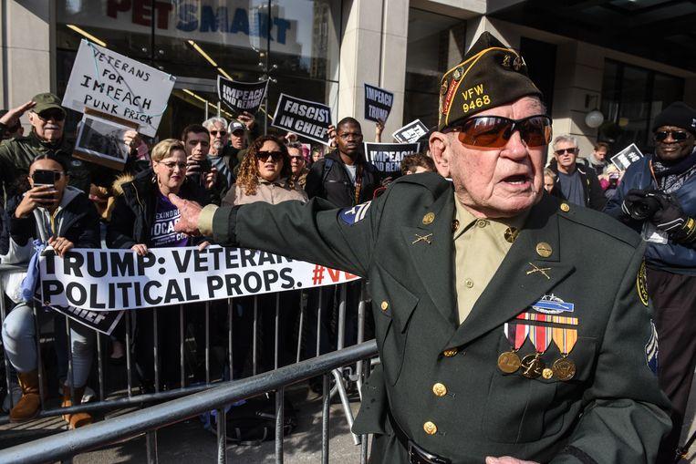 Een veteraan maakt zich kwaad op de anti-Trump-demonstranten tijdens de Veteranendag maandag in New York. De president hield daar een toespraak. Beeld Getty Images