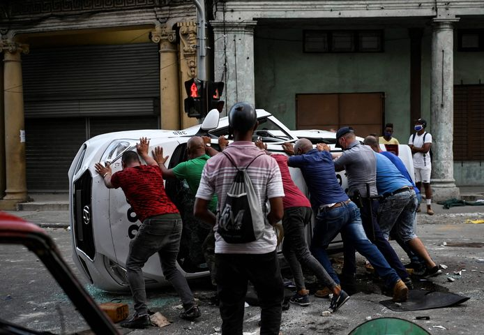 """TOPSHOT - People push an overturned car in the street in the framework of a demonstration against Cuban President Miguel Diaz-Canel in Havana, on July 11, 2021. - Thousands of Cubans took part in rare protests Sunday against the communist government, marching through a town chanting """"Down with the dictatorship"""" and """"We want liberty."""" (Photo by YAMIL LAGE / AFP)"""