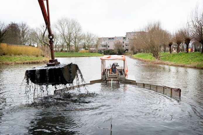 BREDA - Mark Waasdorp vaart met een baggerschuifboot door de watergang bij de Westerhagelaan in de Haagse Beemden. Waasdorp duwt het slib bij elkaar zodat kraanmachinist Ewout de Kuiper het makkelijk op kan graven.