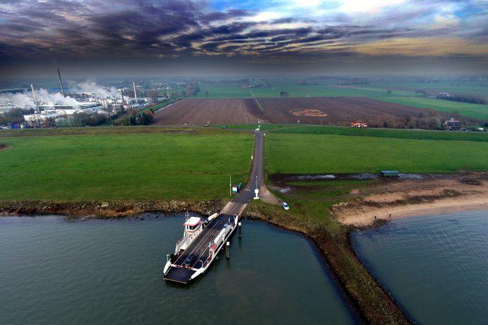 Autoveer Brakel II legt aan bij de veerstoep in Herwijnen. Op de achtergrond links ligt bedrijventerrein Zeiving in vuren. De veer pont wordt geëxploiteerd door Riveer.