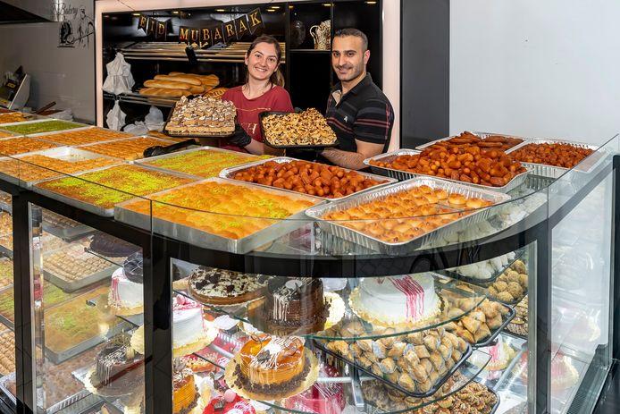 Elif Canakcioglu-Yilmaz (links) & haar partner Emrah Yilmaz in hun zaak bakkerij Asya Deluxe in Roosendaal tussen de taarten, baklava en allerlei zoetwaar voor het suikerfeest.