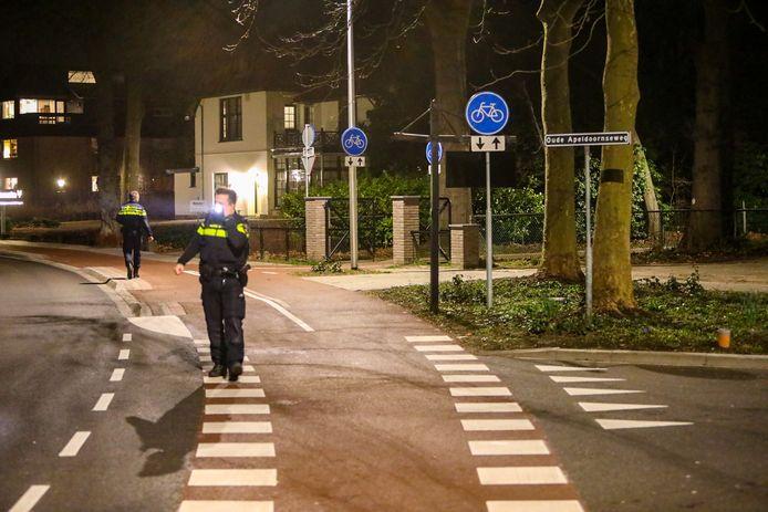 Twee politieagenten speuren op de plek van het ongeval.