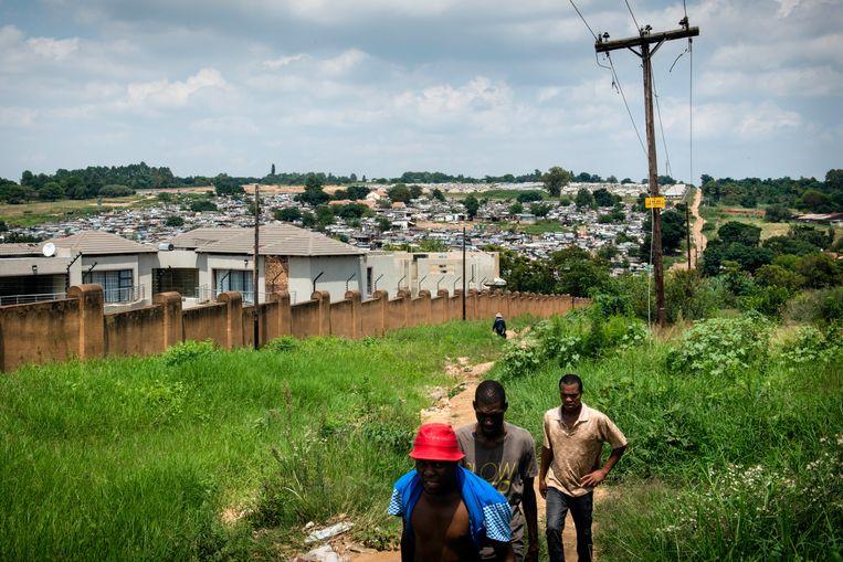 Inwoners van de sloppenwijk Msawawa lopen langs een ommuurd wooncomplex aan de uiterste rand van Johannesburg.  Beeld Bram Lammers
