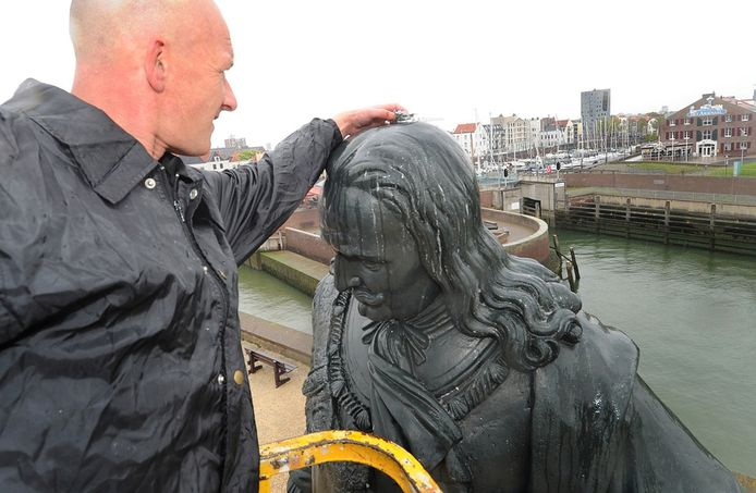 Rudy Marinisse brengt een doosje met gel aan op het standbeeld van Michiel de Ruyter.