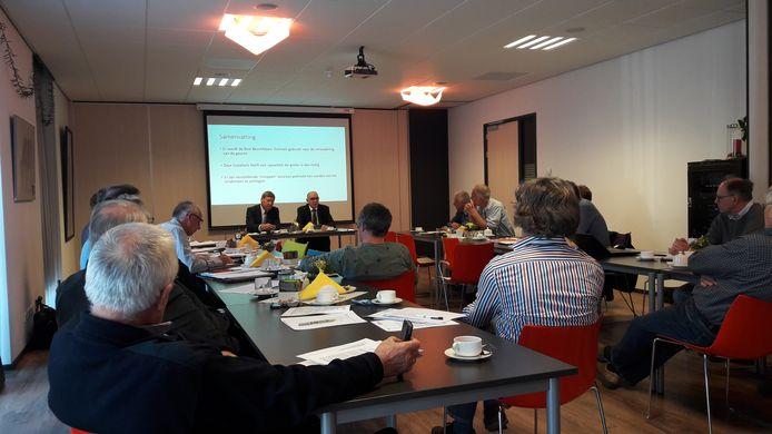 """Wethouder Jaap Sinke (rechts achter tafel) geeft de aanwezigen in Waarde uitleg over het werkbezoek van de gemeenteraad aan de biovergister in Bemmel: ,,Ik rook buiten niets."""""""