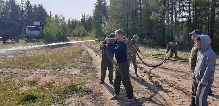 Brandweerlieden en burgers proberen bosbranden te voorkomen.  Beeld REUTERS