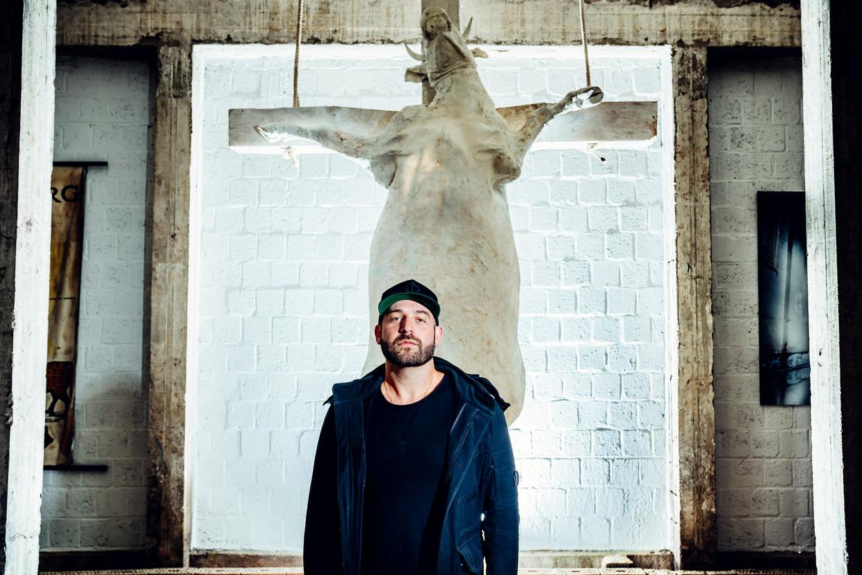 Tom Herck en zijn 'Holy Cow'. Zijn kunstwerk hangt nu in Sint-Truiden. Beeld © Stefaan Temmerman