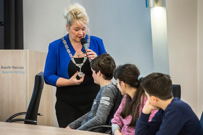 Burgemeester Marjon de Hoon-Veelenturf geeft les in de raadzaal van de gemeente en vertelt onder andere over de betekenis van de tweezijdige medaille, die aan haar ambtsketen hangt.