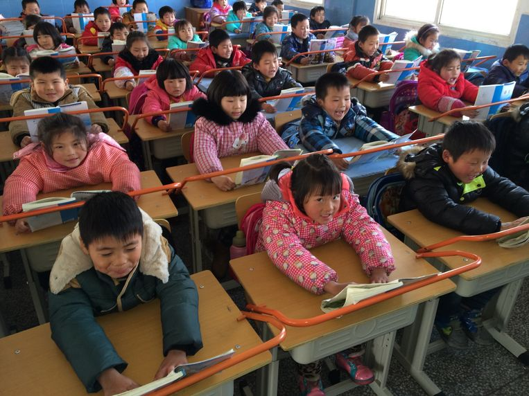 Kinderen in een klas in Wuhan in China moeten hun boeken tegen de ijzeren stangen op hun bureaus houden als ze lezen, om hun gezichtsvermogen te beschermen.  Beeld Getty