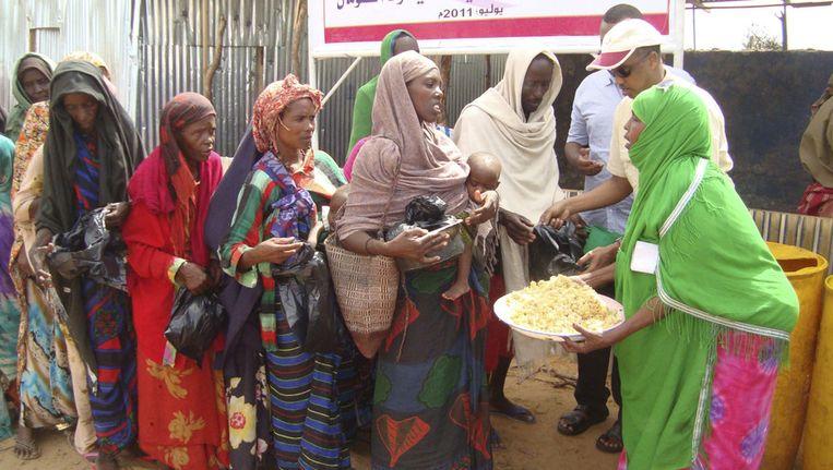 Somaliërs krijgen eten en drinken bij een voedingscentrum in Mogadischu. Beeld ap