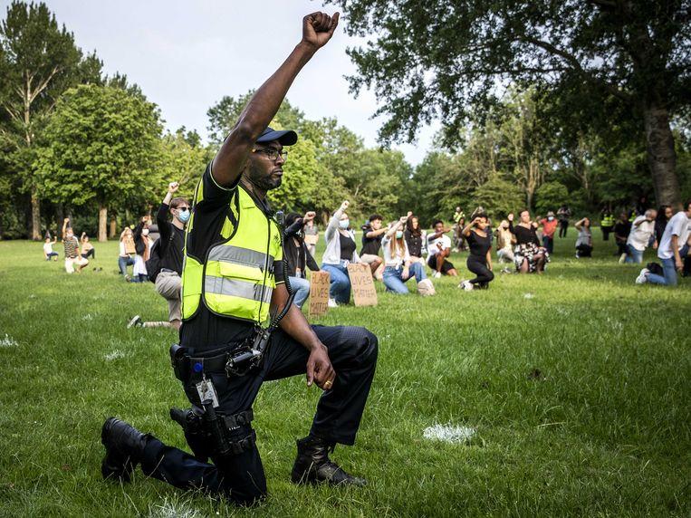 Een politieagent knielt deze zomer tijdens een demonstratie tegen politiegeweld en racisme, naar aanleiding van de dood van de Amerikaan George Floyd.  Beeld ANP / Remko de Waal