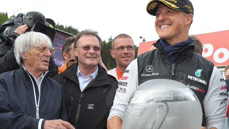 Michael Schumacher showt een glazen replica van zijn eerste helm op het circuit van Spa. Geheel links Formule 1-baas Bernie Ecclestone. Beeld epa