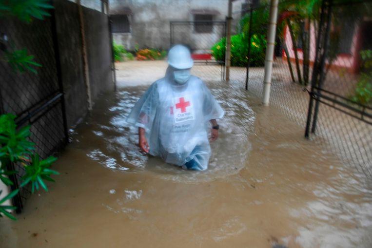 Een medewerker van het Guatemalteekse Rode Kruis waadt door een ondergelopen straat in Puerto Barrios in Guatemala, dat donderdag 5 november werd getroffen door orkaan Eta.  Beeld AFP
