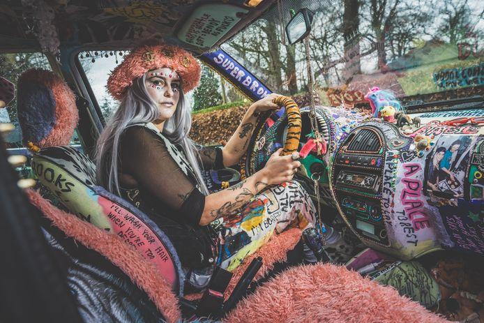 Nina Vandenbempt in haar auto met het spectaculaire interieur: een explosie van kleuren. ,,Ik merk dat veel mensen blij worden als ze mijn auto zien.''