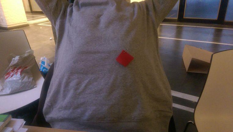 Een rood stukje vilt, opgespeld met een veiligheidsspeld. Beeld Heleen van Lier
