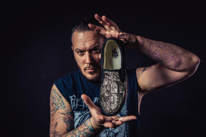 Tattoo artiest Jadran Beauprez met een paar van zijn beschilderde schoenen, die intussen ook aan de voeten hangen van een reeks sterren in de Verenigde Staten, zoals hiphoplegende Snoop Dogg.