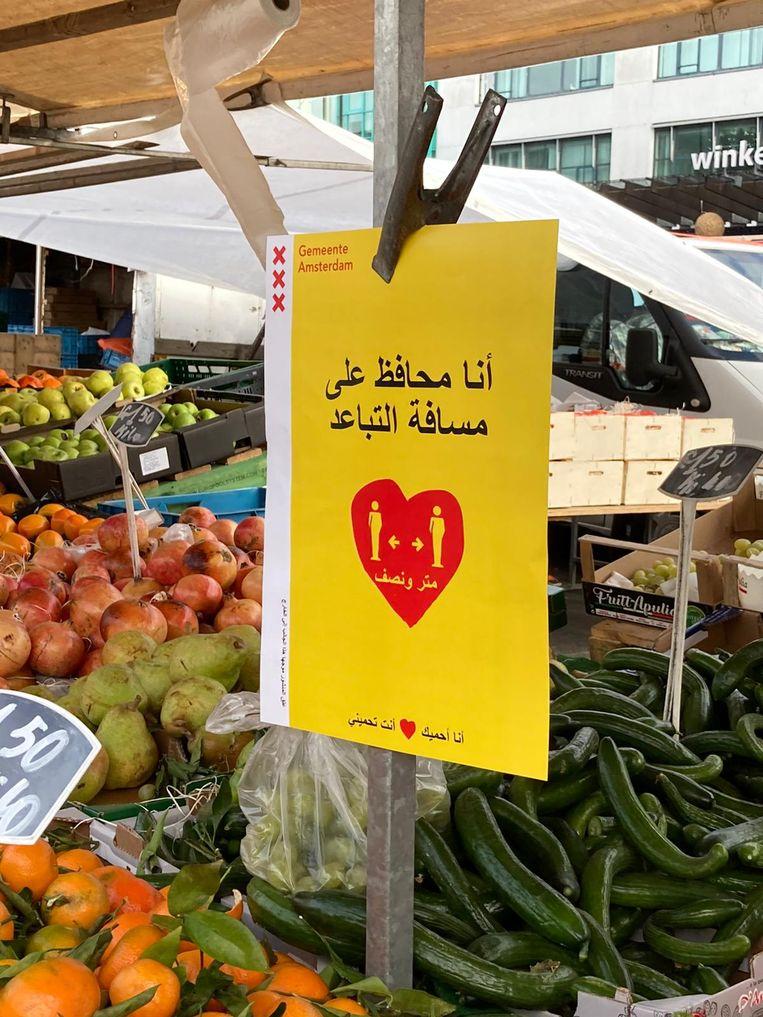 Ook op de Amsterdamse markten wordt in meerdere talen gevraagd afstand van elkaar te houden. Beeld Joshua Serrao