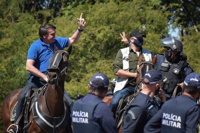 De Braziliaanse president Bolsonaro beklom zondag een paard van de militaire politie tijdens een betoging in de hoofdstad Brasília.