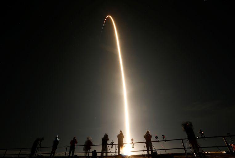 Mensen kijken in Cape Canaveral, Florida naar de lancering van de SpaceX Falcon 9-raket met daaraan de Crew Dragon capsule . Beeld REUTERS