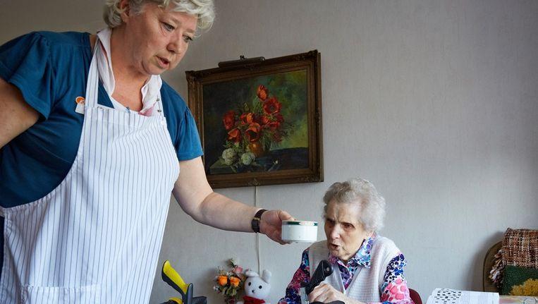 Een bewoonster van woonzorgcentrum Houthaghe krijgt een kopje bouillon op haar kamer. Beeld ANP
