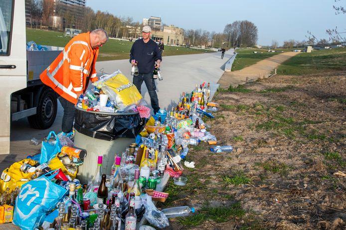 Vrijwilligers en medewerkers van de Diamantgroep ruimen de rommel op na een lentedag in het park
