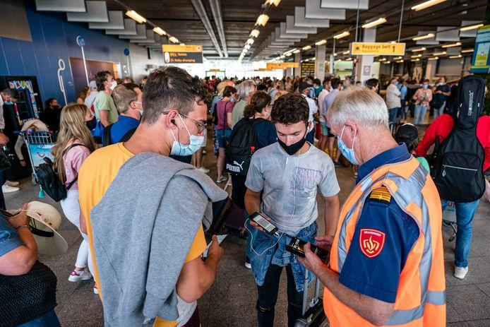 Reizigers die terugkeren van vakantie worden op Eindhoven Airport gecontroleerd op hun coronabewijs. Veel coronabesmettingen blijken herleidbaar tot vakanties in Spanje, Griekenland, Frankrijk, Turkije en Marokko.
