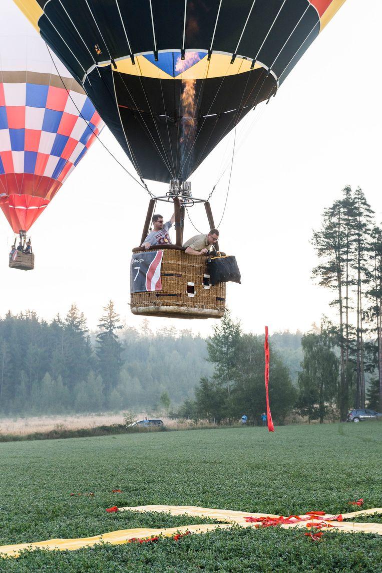 Een competitiebeeld. Ballons scheren laag over de grond om zo dicht mogelijk bij het kruis te komen, maar mogen de grond niet aanraken. Beeld Andreas Biedermann