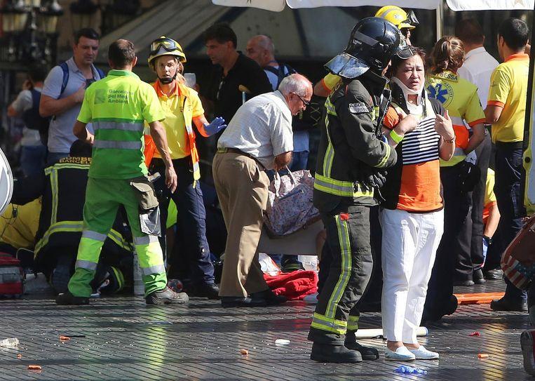 Hulpdiensten helpen gewonden na de aanslag op de Ramblas in Barcelona. Beeld AP