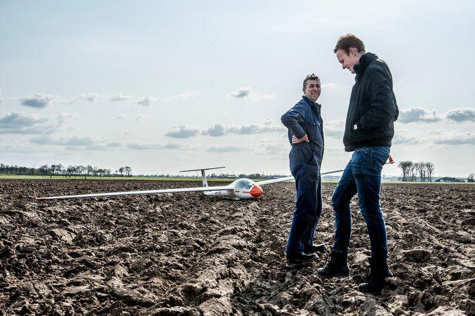 De gestrande piloot Steffen Landman (rechts) in gesprek met landeigenaar Jaap van der Linde.