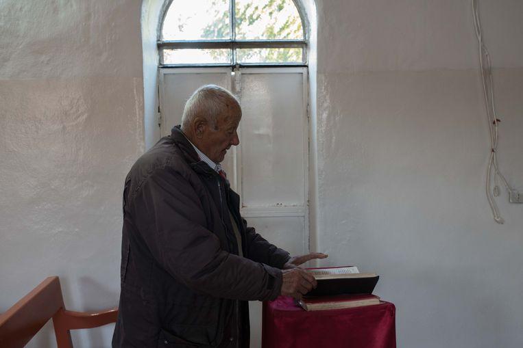 Zeiyye Isaac leest uit de Bijbel tijdens de kerkdienst in Tel Jumaa. Beeld Vincent Haiges