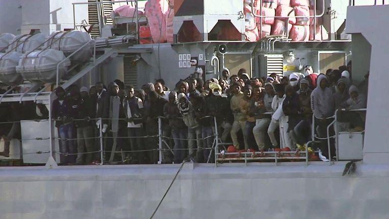 Migranten lopen naar de railing van een marineboot als de haven van Messina in zicht komt. Beeld ap