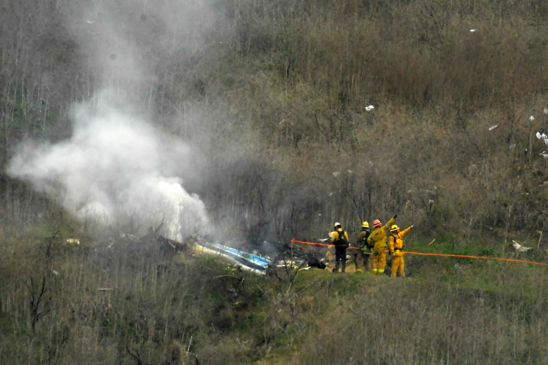 Brandweerlui bij het wrak van helikopter S-76B.