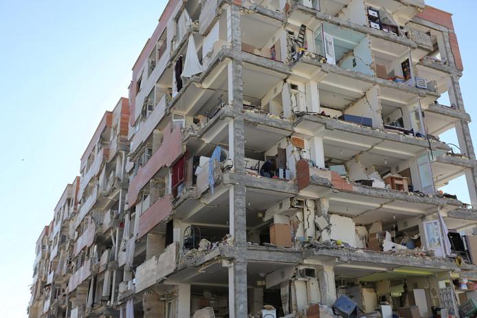 Een Iraanse bewoner van een door de aardbeving getroffen flat in Sarpol-e Zahab haalt, met gevaar voor eigen leven, wat bezittingen uit zijn huis op de derde verdieping. Foto Tasnim News