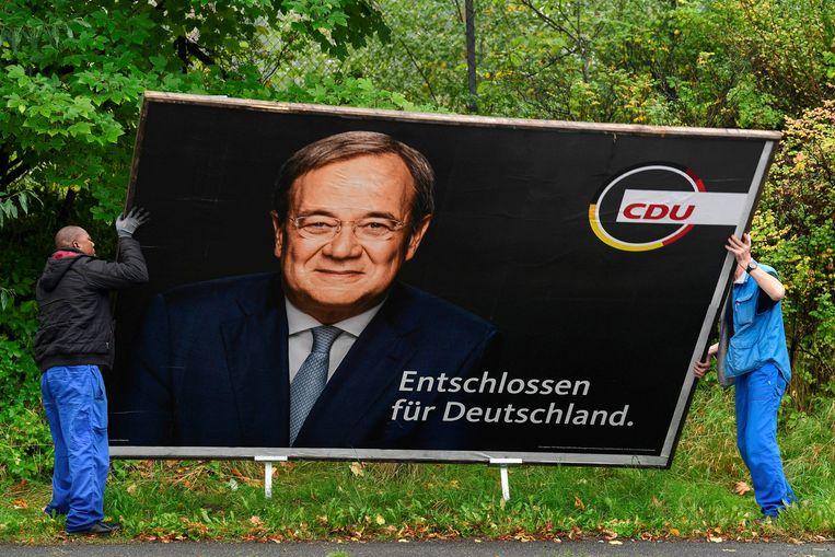 Een billboard met een foto van CDU-lijsttrekker Armin Laschet wordt verwijderd.  Beeld REUTERS